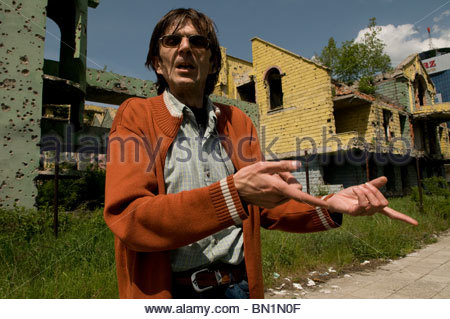 A Bosnian man shows shrapnel damage from the 1992-95 war in downtown Sarajevo, Bosnia Herzegovina - Stock Photo