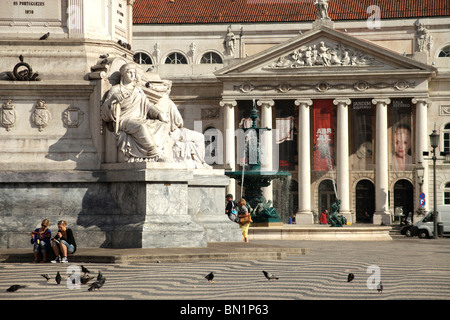 Monument and fountain in front of the National theater Dona Maria II on the square Praca de Dom Pedro IV or Rossio - Stock Photo