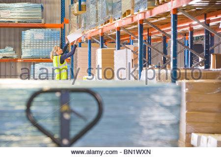 Female warehouse worker lifting box from shelf - Stock Photo