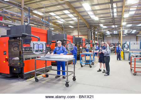 Workers and machinery in factory that manufactures aluminium light fittings - Stock Photo