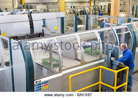 Worker operating computer controlled machinery in factory that manufactures aluminium light fittings - Stock Photo