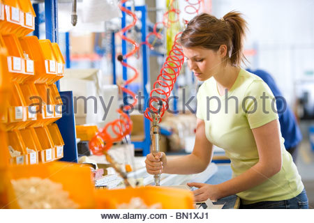 Worker operating machinery on production line in factory that manufactures aluminium light fittings - Stock Photo