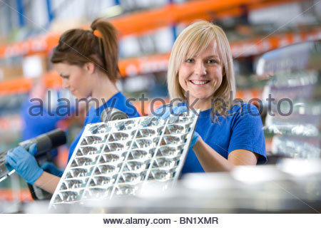 Portrait of smiling worker holding aluminium light fittings in factory - Stock Photo