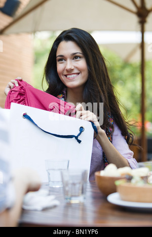 Woman sitting in cafe with friend, showing clothing in shopping bag - Stock Photo