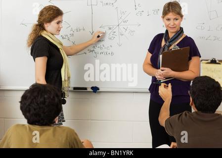 Teacher explaining mathematics to students in classroom - Stock Photo