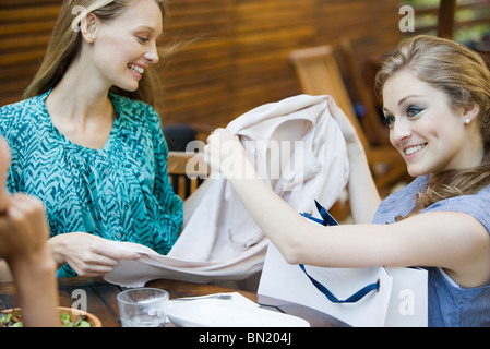 Friends together in outdoor cafe, one woman showing new clothing in shopping bag - Stock Photo