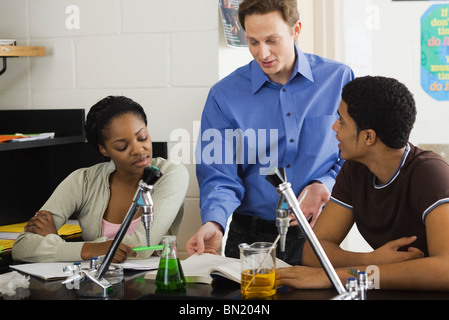 Chemistry teacher explaining experiment to students - Stock Photo