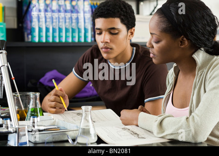 Students working on assignment in chemistry class - Stock Photo