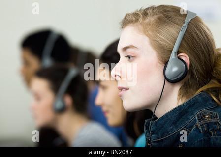 High school students listening to headphones, profile - Stock Photo