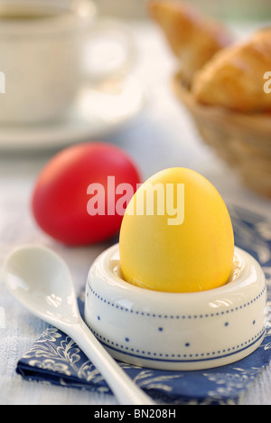 Yellow Easter Egg in an Eggholder, Red Egg lying at the Side - Stock Photo