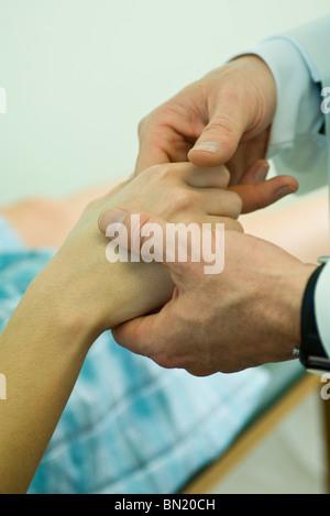 Doctor examining patient's fingers - Stock Photo