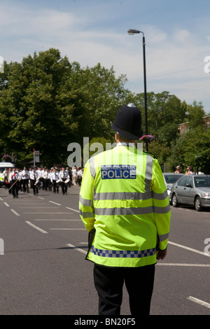 Metropolitan Police Officer in Hi-viz jacket back to camera. - Stock Photo