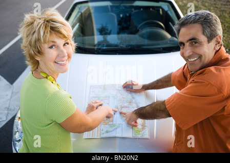 Mature couple on road trip checking map - Stock Photo