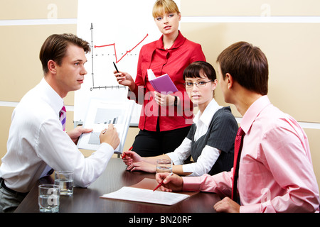 Image of smart teacher looking at students while explaining new topic - Stock Photo