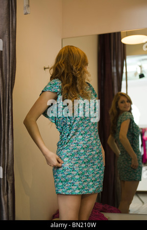 Shopper trying on dress in fitting room - Stock Photo