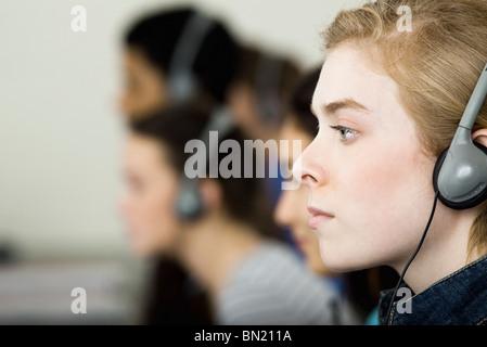 Student listening to headphones, profile - Stock Photo