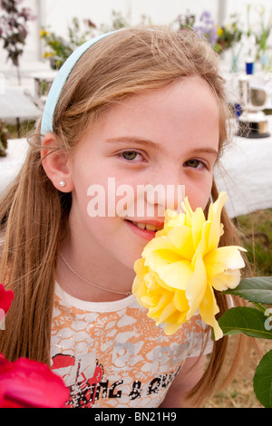 Young girl smelling a yellow rose, Ireland - Stock Photo