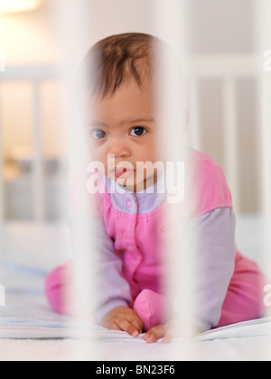 Cute seven month old baby girl sitting inside a crib behind bars - Stock Photo