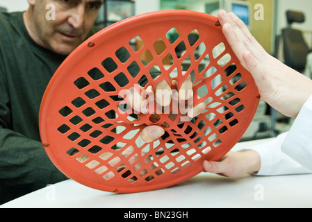 Patient using hand exercise web for occupational therapy treatment - Stock Photo