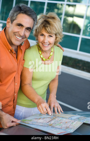 Mature couple looking at map together planning road trip - Stock Photo