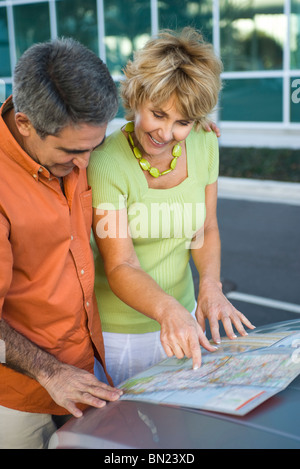 Mature couple looking at road map together, discussing route for road trip - Stock Photo