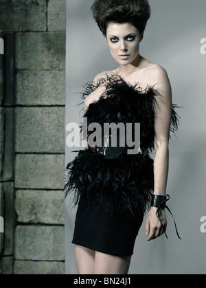 High fashion photo of a beautiful woman wearing elegant black feathery dress