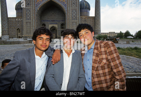 TGhree young Uzbek boys stand in Registan Square, in the city of Samarkand, Uzbekistan - Stock Photo