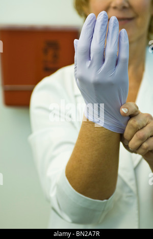 Putting on disposable latex glove - Stock Photo