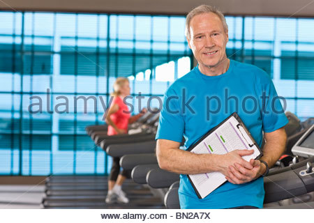 Portrait of man with clipboard standing on treadmill in health club - Stock Photo