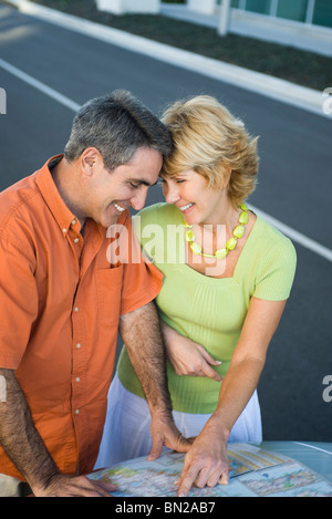 Mature couple looking at road map together planning route for road trip - Stock Photo
