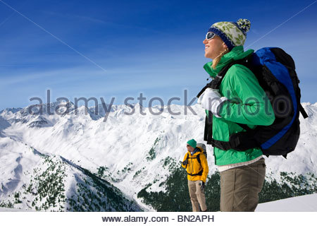 Couple backpacking on snowy mountain - Stock Photo