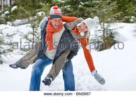 Happy couple piggybacking in snowy woods - Stock Photo