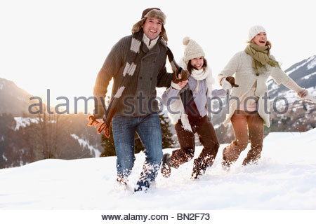 Family running outdoors in snow - Stock Photo