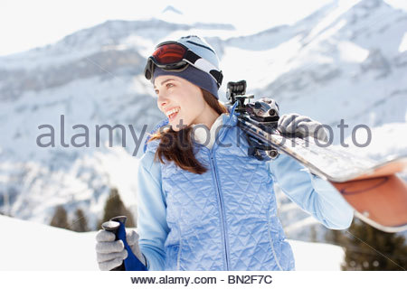Woman carrying skis - Stock Photo