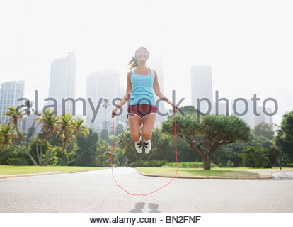 Woman skipping rope in park - Stock Photo