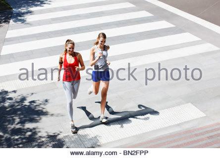 Friends running across urban crosswalk - Stock Photo