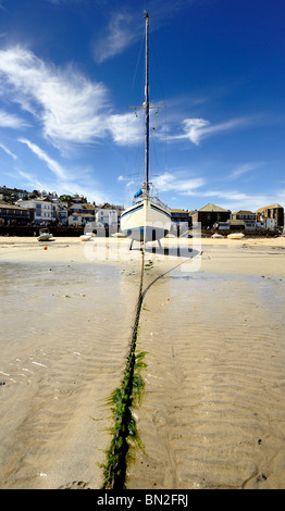 A yacht stands in the sand at low tide - Stock Photo