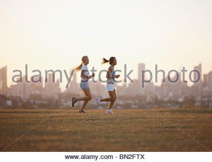 Friends running through field - Stock Photo