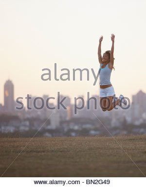 Woman jumping in urban park - Stock Photo