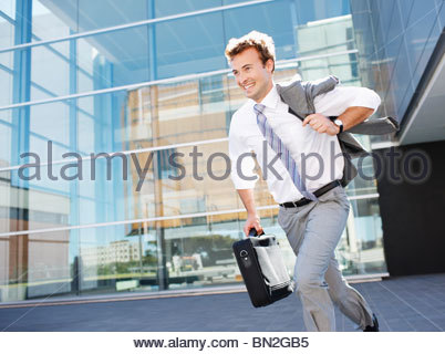 Businessman running with briefcase - Stock Photo