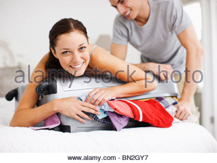 Couple trying to close full suitcase - Stock Photo