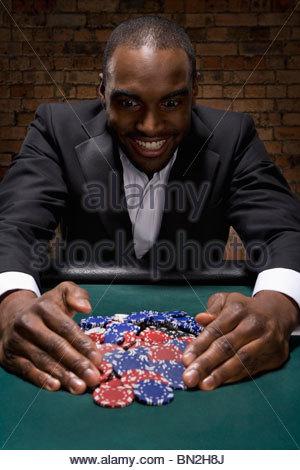Man gathering poker chips in casino - Stock Photo