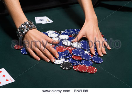 Woman gathering poker chips in casino - Stock Photo