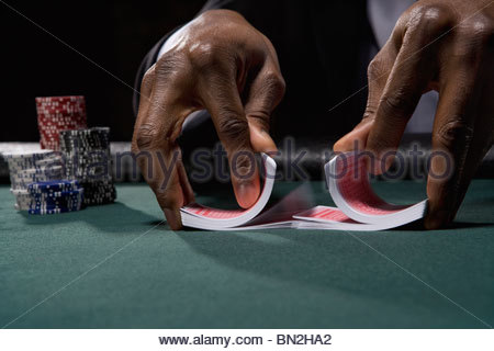 Dealer shuffling cards in casino - Stock Photo
