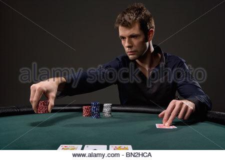Man playing poker in casino - Stock Photo
