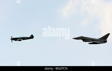 Royal Air Force Typhoon flies with a Spitfire at Biggin Hill in Kent England - Stock Photo