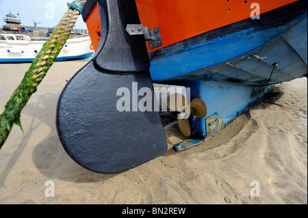 Close up of fishing boat rudder and propeller in the sand at low tide - Stock Photo