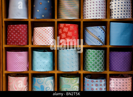 colourful neck ties in display rack - Stock Photo