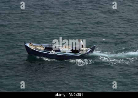 Man in a small fishing boat on the greek island of Corfu. - Stock Photo
