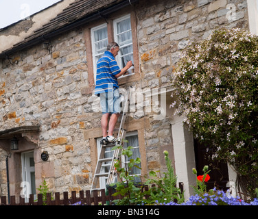 A man painting the windows on his cottage, Peak District Derbyshire England UK - Stock Photo